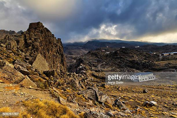 Evening clouds over ski resort Whakapapa Village, deserted in summer on slopes of volcanic Mount Ruapehu, New Zealand. Meads Wall, a volcanic rock...
