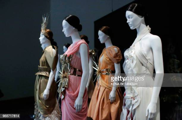 Evening dresses are on display during the press preview for the annual fashion exhibit Heavenly Bodies Fashion and the Catholic Imagination at The...