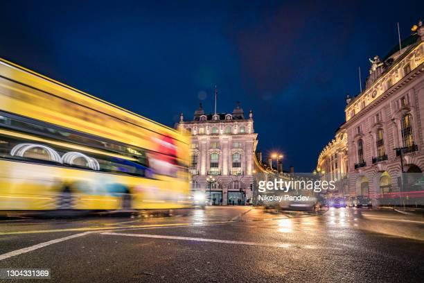 英国ロンドンのピカデリーサーカスで濡れた交差点を通過する激しい交通と夕方の照明反射 - 創造的なストック画像 - ウェストエンド ストックフォトと画像