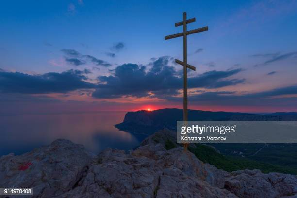Evening landscape. View from the mountain to the coastline, towns. Picturesque sunset sky. A memorial cross in the foreground.