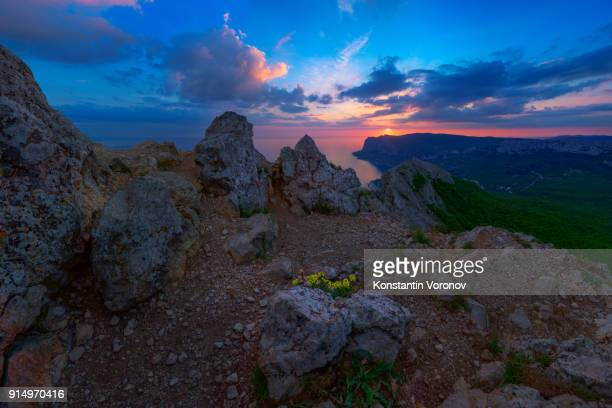Evening landscape. View from the mountain to the coastline, towns. Picturesque sunset sky. Rocks in the foreground.