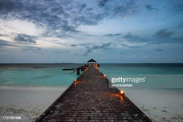evening light in the maldives - elevated walkway stock pictures, royalty-free photos & images