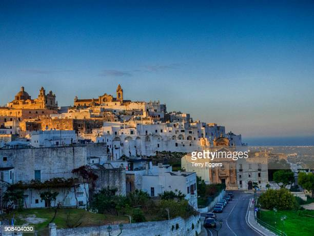 evening light on the white old town - ostuni stock photos and pictures