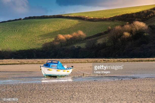 Evening light over a boat moored in the Gannel River at low tide in Newquay in Cornwall.