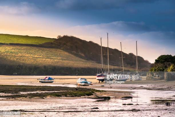 Evening light over boats moored and beached on the foreshore of the Gannel River at low tide in Newquay in Cornwall.