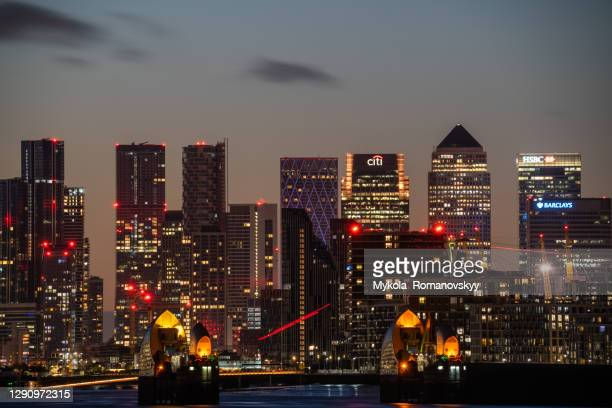 evening photo of the canary wharf which is behind north greenwich block of buildings, view from the east(woolwich). - the o2 england stock pictures, royalty-free photos & images