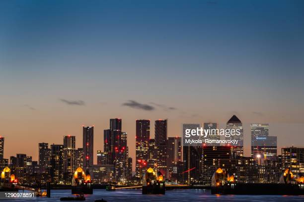 evening photo of the canary wharf which is behind north greenwich block of buildings and the thames barrier. view from the east(woolwich). - the o2 england stock pictures, royalty-free photos & images