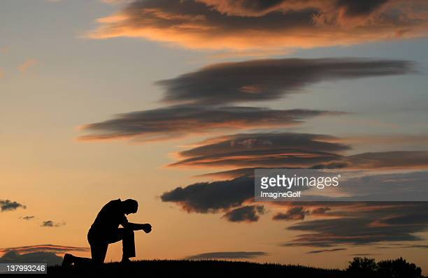 evening prayer silhouette of unrecognizable man kneeling - kneeling stock pictures, royalty-free photos & images