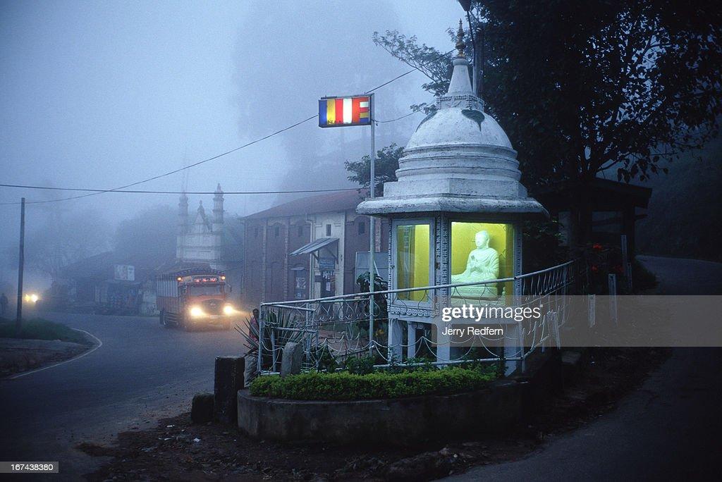 Evening rolls in as a truck rolls by a Buddhist shrine along the roadside in Haputale..