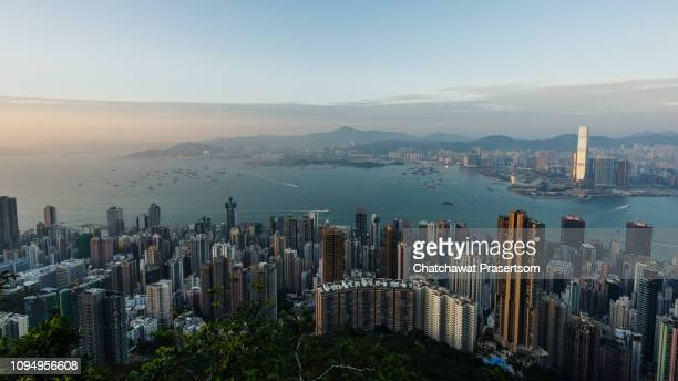 evening scene of hong kong city and victoria harbour - hong kong stock pictures, royalty-free photos & images