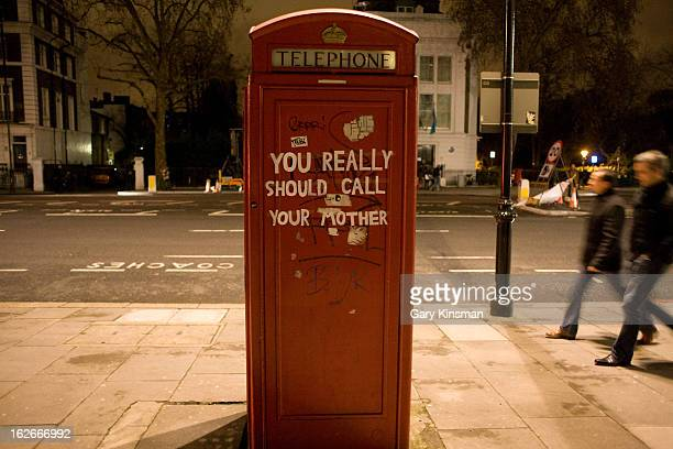 "Evening shot of graffiti which reads ""you really should call your mother"" on the back on a red telephone box in South Kensington, Central London, 2011"