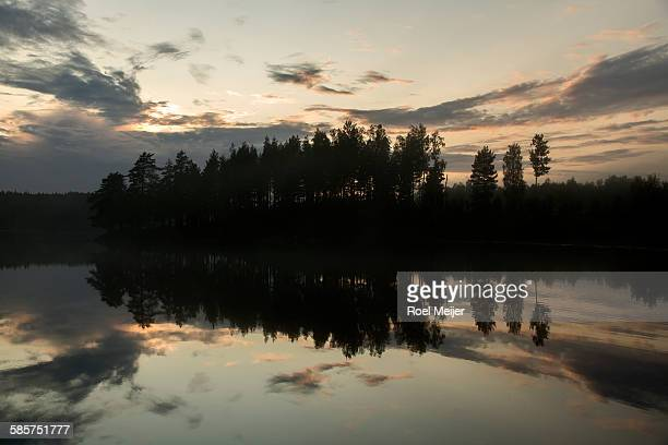 evening sky and trees mirroring in swedish lake - dalsland stock photos and pictures