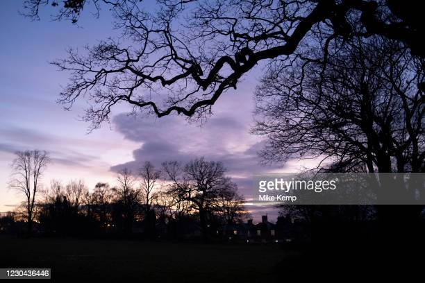 Evening sky through silhouette of trees in Highbury Park in Kings Heath on 30th December 2020 in Birmingham, United Kingdom. Highbury Park is a...