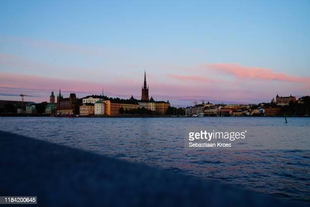 evening sun at old stockholm, riddarholmen, sweden - riddarholmkirche stock-fotos und bilder