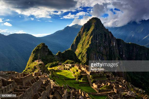 Evening sun illuminates Huayna Picchu mountain over Machu Picchu ruins, Peru