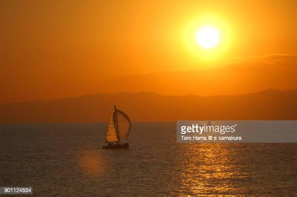 Evening sun on Izu Peninsula and a yacht on Sagami Bay in Kanagawa prefecture in Japan