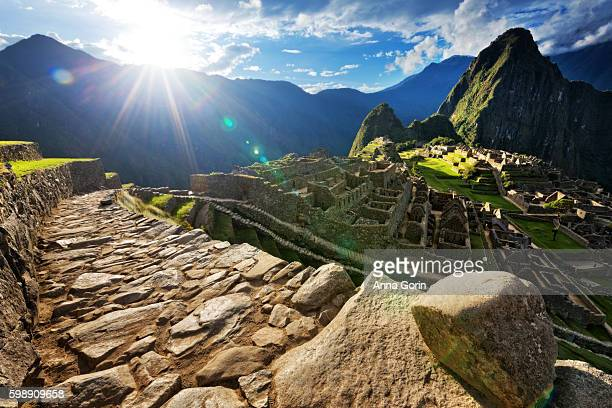 Evening sunburst over deserted paved pathway overlooking Machu Picchu ruins, Peru