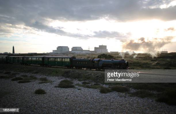 Evening sunlight bathes Dungeness nuclear power station as a steam train from the Romney Hythe and Dymchurch railway passes by on October 21 2013 in...
