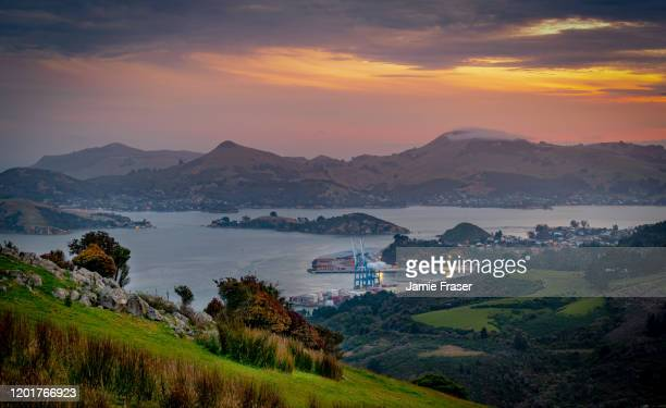 evening sunset hues over otago harbour, port chalmers and peninsula - dunedin new zealand stock pictures, royalty-free photos & images