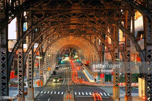 evening traffic with light trails of moving cars belwo a steel viaduct construction - rainer grosskopf stock pictures, royalty-free photos & images