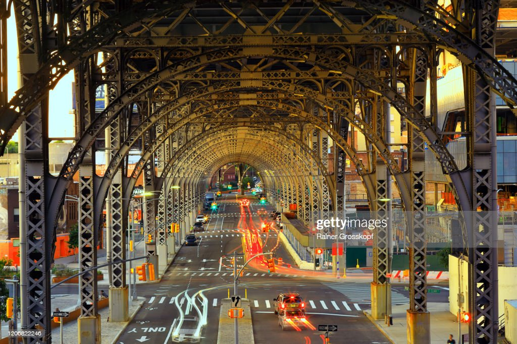 Evening traffic with light trails of moving cars belwo a steel viaduct construction : Stock-Foto
