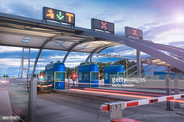 Evening view of cars passing through toll booth at bridge