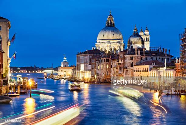 evening view of grand canal traffic and basilica di santa maria della salute, venice, italy - vaporetto stock pictures, royalty-free photos & images