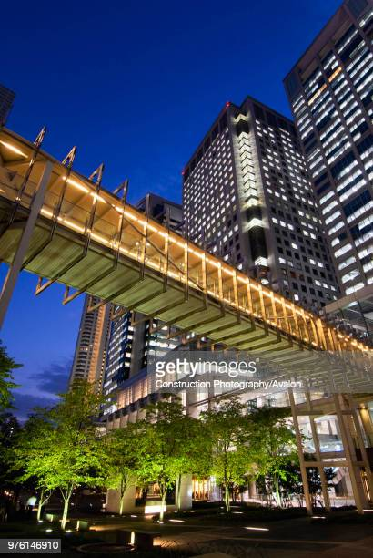 Evening view of modern highrise office buildings footbridge and urban landscaped park in Shinagawa central Tokyo Japan