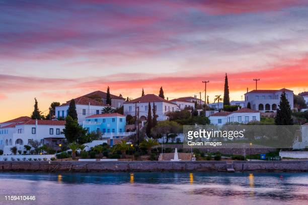 evening view of spetses village from the harbour pier, greece. - spetses stock pictures, royalty-free photos & images