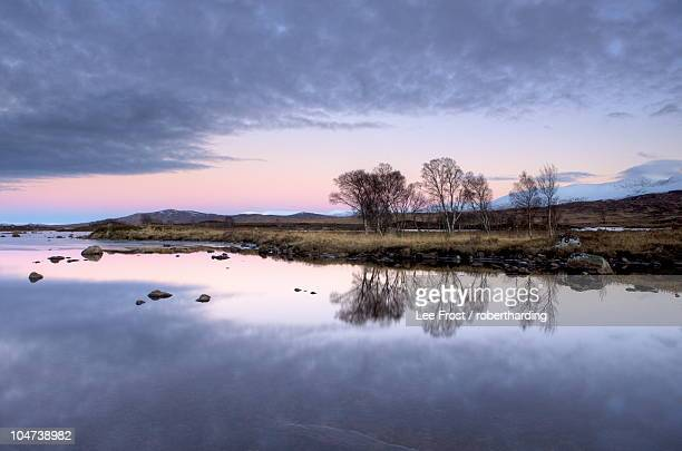 evening view over flat calm loch ba with pink afterglow in sky, reflected in loch and snow-capped mountains in distance, rannoch moor, near fort william, highland, scotland, united kingdom, europe - newpremiumuk stock pictures, royalty-free photos & images