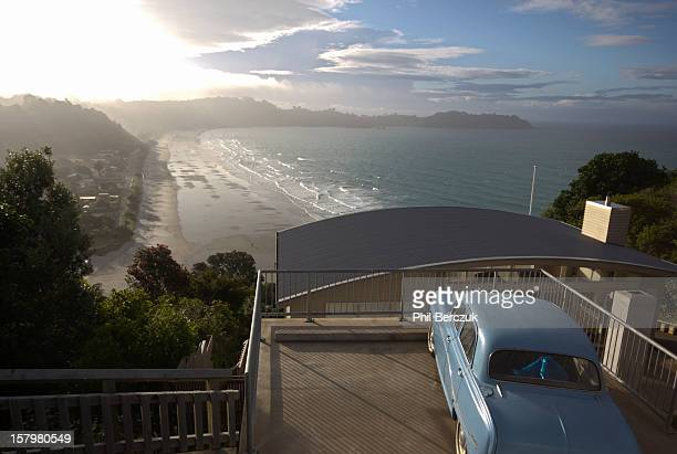 Evening view over the beach at Onetangi Bay with pale blue 60's car in the foreground, new year's eve 2011. Waiheke Island is in the Hauraki Gulf of...