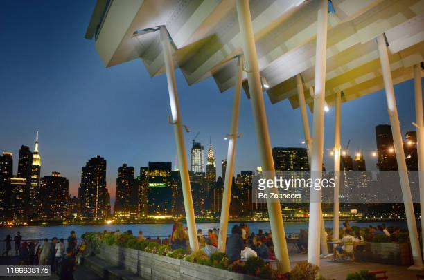 evening wiew of manhattan from lic landing, hunters point south waterfront park in long island city, nyc - bo zaunders stock pictures, royalty-free photos & images