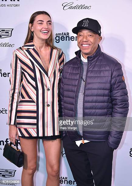 Event chair Alina Baikova and Russell Simmons attend the 2016 amfAR GenerationCure Holiday Party at Cadillac House on December 7 2016 in New York City