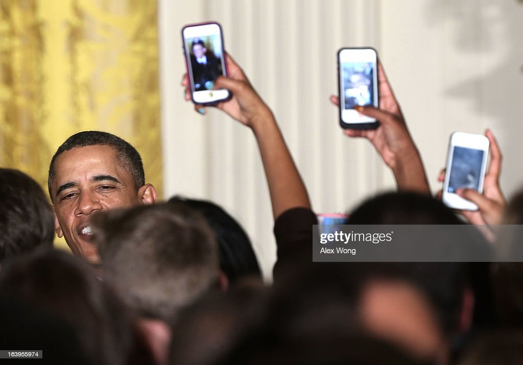 Event guests try to take photos of U.S. President Barack Obama with their cellular phones during a Women's History Month Reception in the East Room of the White House March 18, 2013 in Washington, DC. President Obama was accompanied by first lady Michelle Obama to participate in the event.