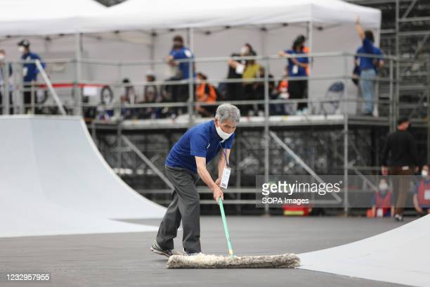 Event organization staff wipes water off the competition area after a rain shower during the Ready Steady Tokyo BMX Freestyle Olympic Test Event in...