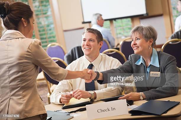 Evento trabalhadores ajudar os participantes da Conferência de verificação