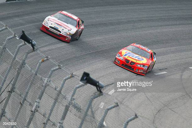 Eventual winner Ricky Craven driver of the Tide Pontiac passes Kurt Busch driver of the Rubbermain Ford on the final lap of the NASCAR Carolina Dodge...