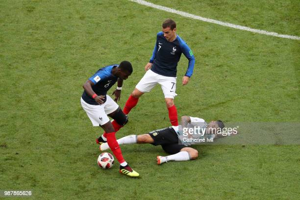 Ever Banega of Argentina tackles Paul Pogba of France during the 2018 FIFA World Cup Russia Round of 16 match between France and Argentina at Kazan...