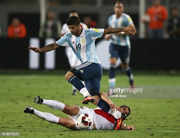 Ever Banega of Argentina tries to avoid the defensive slide by Aldo Corzo of Peru during a match between Peru and Argentina as part of FIFA 2018...