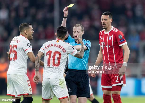 Ever Banega of FC Sevilla is shown a yellow card by referee William Collum during the UEFA Champions League Quarter Final second leg match between...