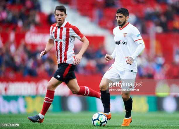 Ever Banega of Sevilla CF duels for the ball with Mikel Vesga of Athletic Club during the La Liga match between Sevilla CF and Athletic Club at...