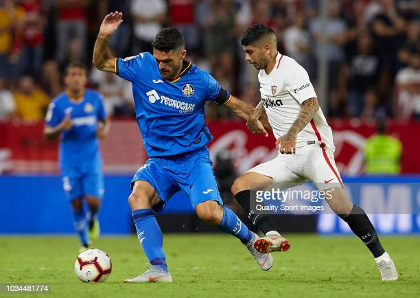 Ever Banega of Sevilla competes for the ball with Jorge Molina of Getafe during the La Liga match between Sevilla FC and Getafe CF at Estadio Ramon...
