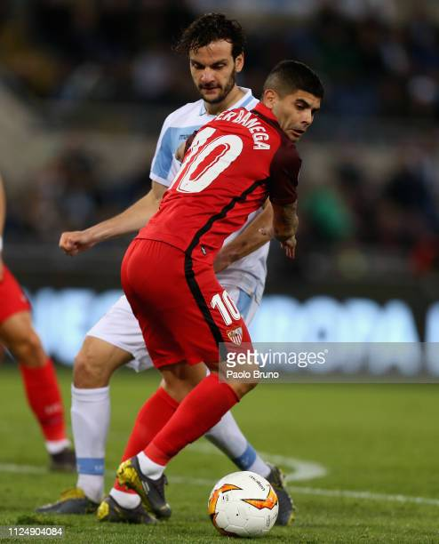 Ever Banega of Sevilla competes for the ball with Marco Parolo of SS Lazio during the UEFA Europa League Round of 32 first leg match between SS Lazio...