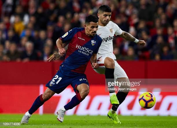 Ever Banega of Sevilla competes for the ball with Serdar Gurler of Huesca during the La Liga match between Sevilla FC and SD Huesca at Estadio Ramon...