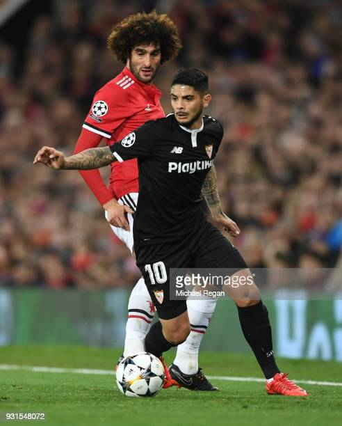 Ever Banega of Sevilla evades Marouane Fellaini of Manchester United during the UEFA Champions League Round of 16 Second Leg match between Manchester...