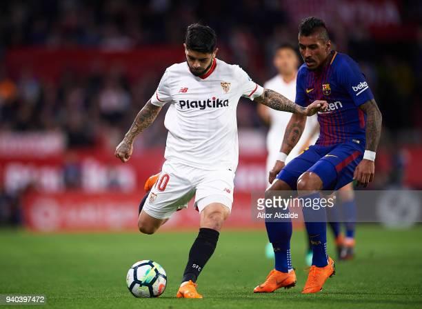Ever Banega of Sevilla FC being followed by Paulinho of FC Barcelona during the La Liga match between Sevilla CF and FC Barcelona at Estadio Ramon...