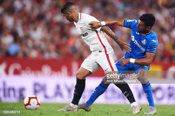 Ever Banega of Sevilla FC competes for the ball with Angel Rodriguez of Getafe CF during the La Liga match between Sevilla FC and Getafe CF at...