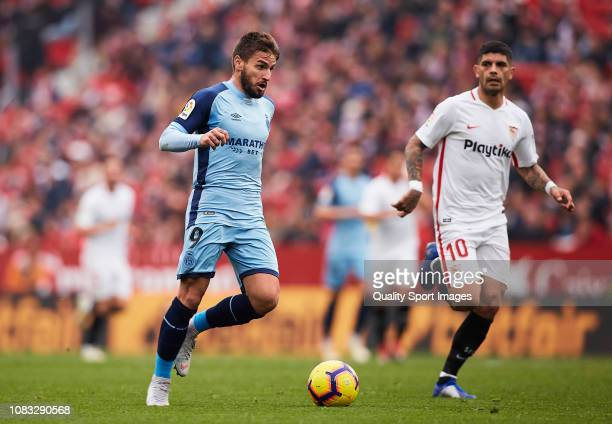 Ever Banega of Sevilla FC competes for the ball with Cristian Portugues of Girona FC during the La Liga match between Sevilla FC and Girona FC at...