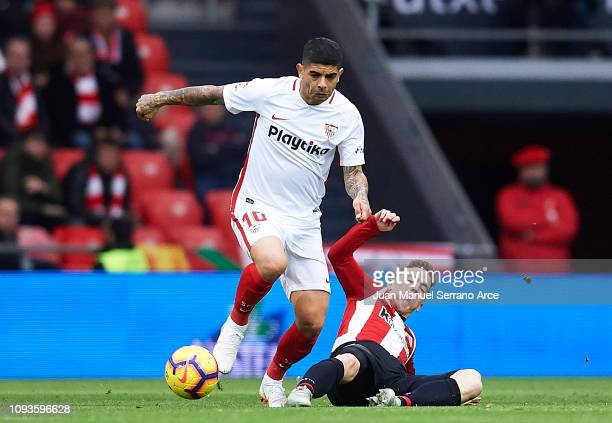 Ever Banega of Sevilla FC competes for the ball with Iker Muniain of Athletic Club during the La Liga match between Athletic Club and Sevilla FC at...