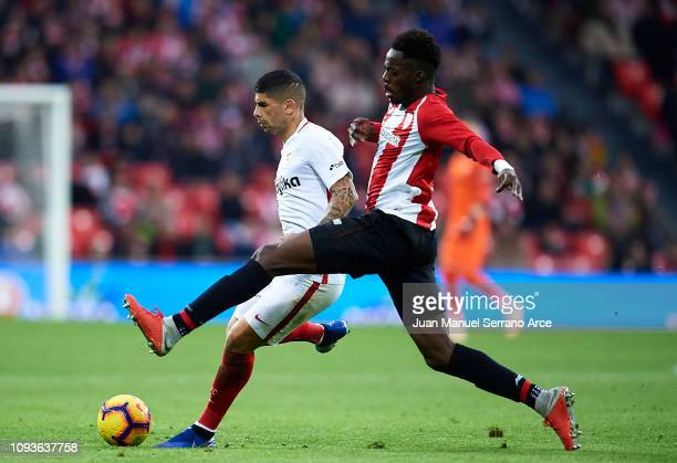 Ever Banega of Sevilla FC competes for the ball with Inaki Williams of Athletic Club during the La Liga match between Athletic Club and Sevilla FC at...